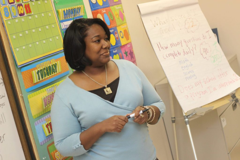 Black or African American Teacher in front of elementary school classroom